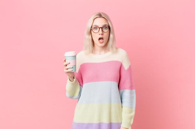 Jolie femme blonde ayant l'air très choquée ou surprise. concept de café