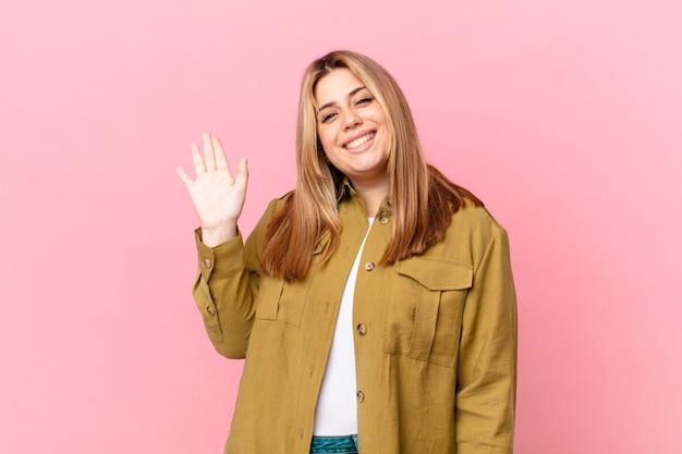 Jolie femme blonde bien roulée souriant joyeusement, agitant la main et vous saluant