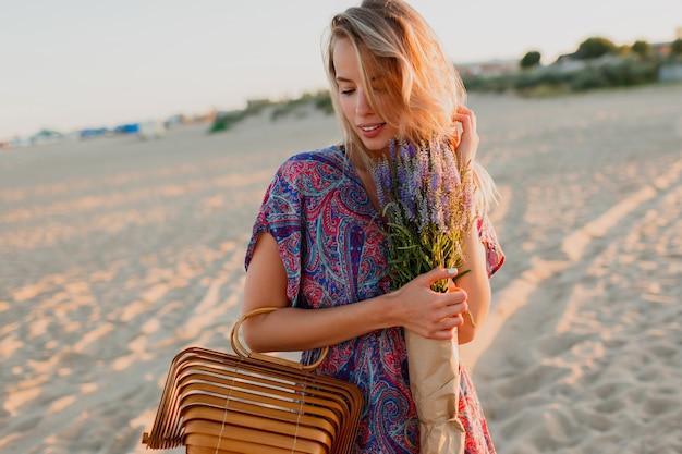Jolie femme blonde avec bouquet de lavande marchant sur la plage. couleurs du coucher du soleil.