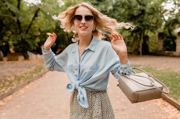Jolie femme blonde candide marchant dans le parc en tenue élégante portant des lunettes de soleil élégantes et sac à main