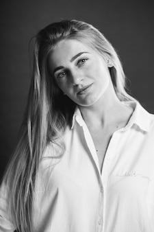 Une jolie femme blonde caucasienne dans une chemise blanche posant sur un fond marron