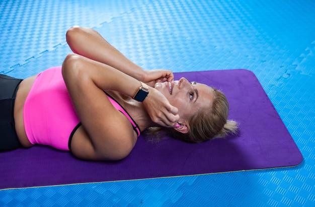 Jolie femme blonde caucasienne en tenue de sport porte un tapis de yoga et écoute de la musique dans des écouteurs dans un cours de fitness