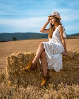 Jolie femme blonde avec une chemise blanche assise sur une meule de foin et posant