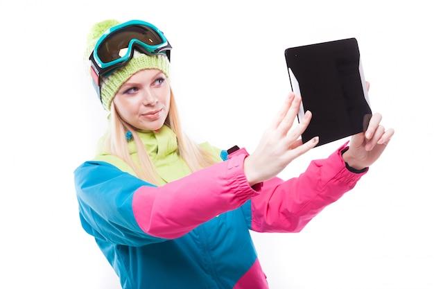 Jolie femme blonde en costume de ski avec tablette