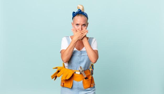 Jolie femme blonde couvrant la bouche avec les mains avec un concept de maison choqué et réparateur