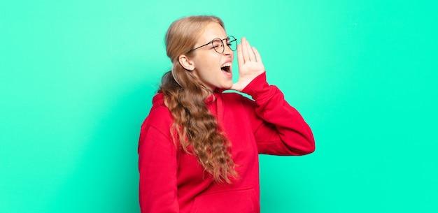 Jolie femme blonde crier fort et en colère pour copier l'espace sur le côté, avec la main à côté de la bouche