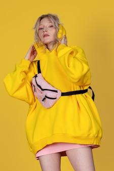 Jolie femme blonde dans un sweat-shirt jaune et un sac à main rose posant sur le fond jaune du studio