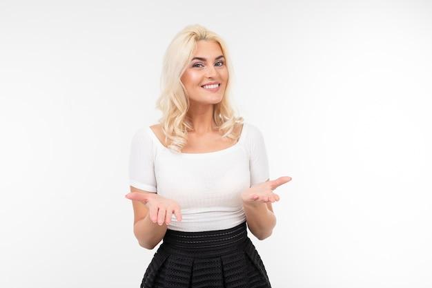Jolie femme blonde dans un t-shirt blanc tend ses mains dans l'espace de copie