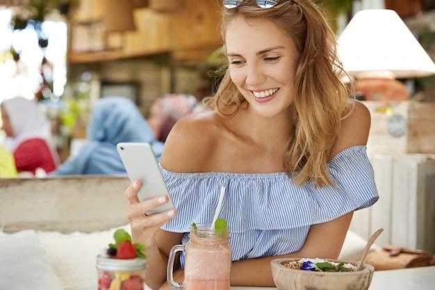 Jolie femme blonde effectue le paiement en ligne, messages en ligne sur téléphone intelligent