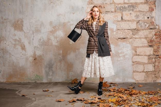 Jolie femme blonde élégante en veste à carreaux marchant contre le mur dans la rue