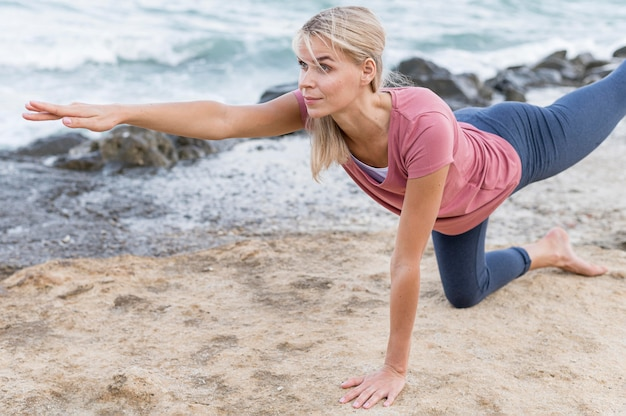 Jolie femme blonde faisant du yoga à l'extérieur