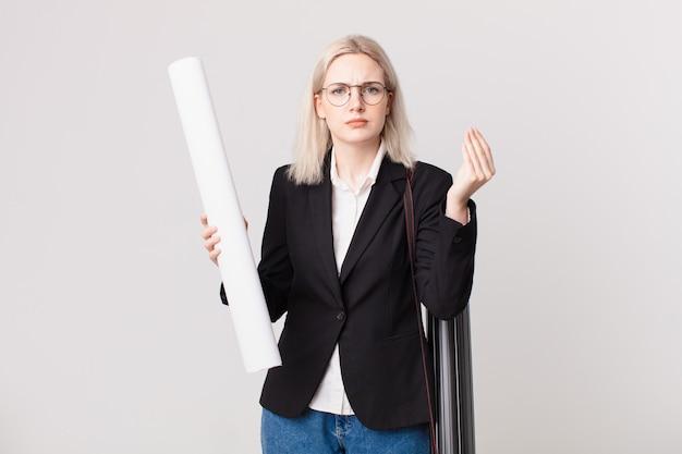 Jolie femme blonde faisant un geste de capice ou d'argent, vous disant de payer. concept d'architecte