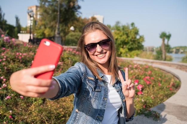 Jolie femme blonde fait selfie sur smartphone