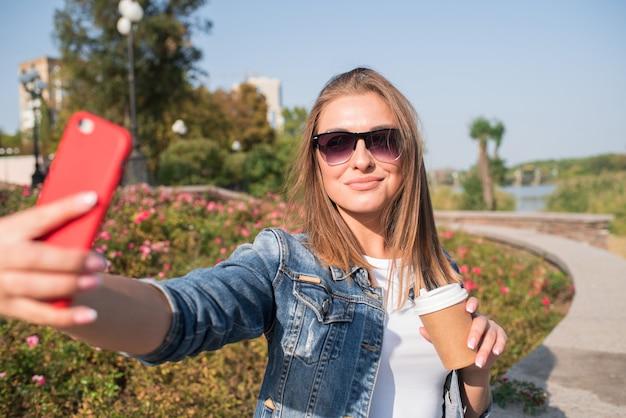 Jolie femme blonde fait un selfie avec une tasse de café