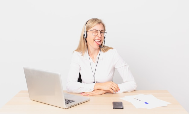 Jolie femme blonde jeune femme blonde avec une attitude joyeuse et rebelle, plaisantant et tirant la langue et travaillant avec un ordinateur portable