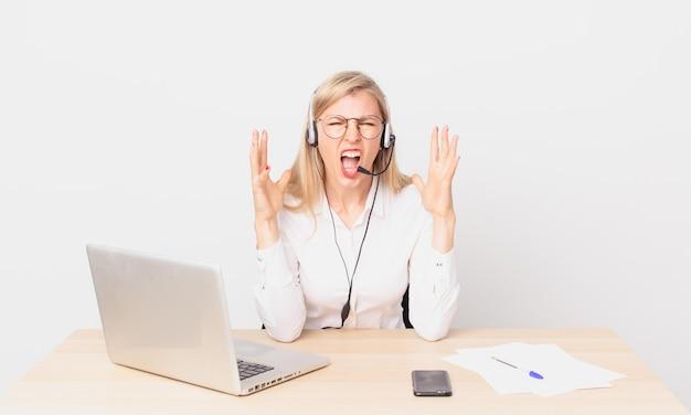Jolie femme blonde jeune femme blonde criant avec les mains en l'air et travaillant avec un ordinateur portable