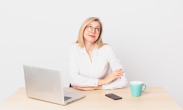 Jolie femme blonde jeune femme blonde haussant les épaules, se sentant confuse et incertaine et travaillant avec un ordinateur portable