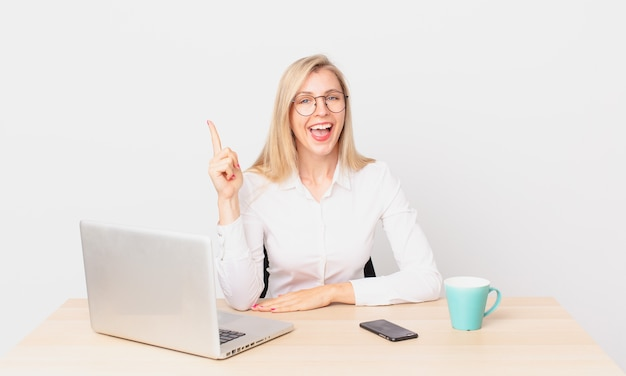 Jolie femme blonde jeune femme blonde se sentant comme un génie heureux et excité après avoir réalisé une idée et travaillé avec un ordinateur portable