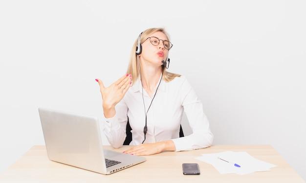Jolie femme blonde jeune femme blonde se sentant stressée, anxieuse, fatiguée et frustrée et travaillant avec un ordinateur portable