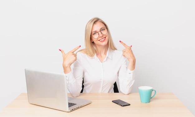 Jolie femme blonde jeune femme blonde souriante pointant avec confiance vers son propre large sourire et travaillant avec un ordinateur portable