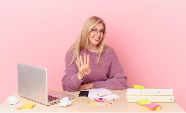 Jolie femme blonde jeune femme blonde souriante et semblant amicale, montrant le numéro quatre et travaillant avec un ordinateur portable