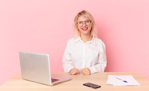 Jolie femme blonde jeune jolie femme à l'air heureux et agréablement surpris. concept de bureau d'espace de travail