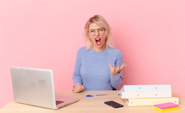 Jolie femme blonde jeune jolie femme à la recherche de colère, agacée et frustrée. concept de bureau d'espace de travail