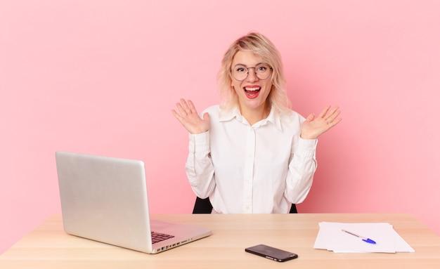 Jolie femme blonde jeune jolie femme se sentant heureuse et étonnée de quelque chose d'incroyable. concept de bureau d'espace de travail