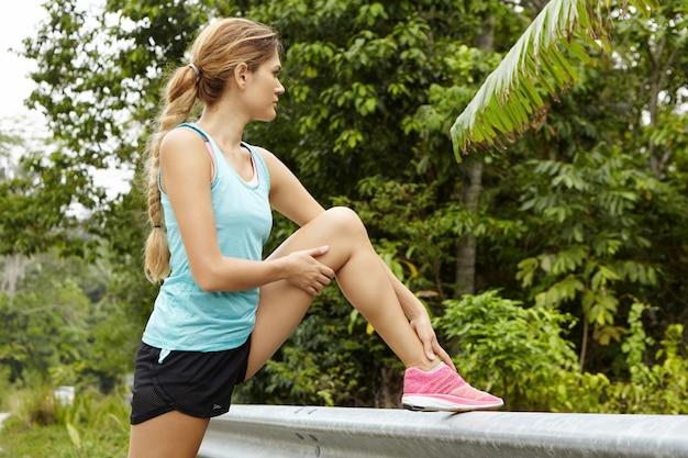 Jolie femme blonde jogger portant des baskets roses examinant sa jambe pour une blessure, reposant son pied sur le garde-corps routier.