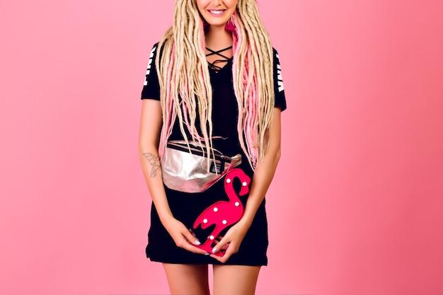 Jolie femme blonde avec de longues dreads blondes tenant un flamant rose en plastique, portant une tenue chic sport élégante, des émotions surprises, un dernier style pop.