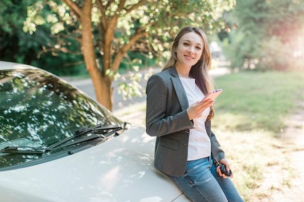 Jolie femme blonde à la mode avec un téléphone intelligent et des clés de voiture