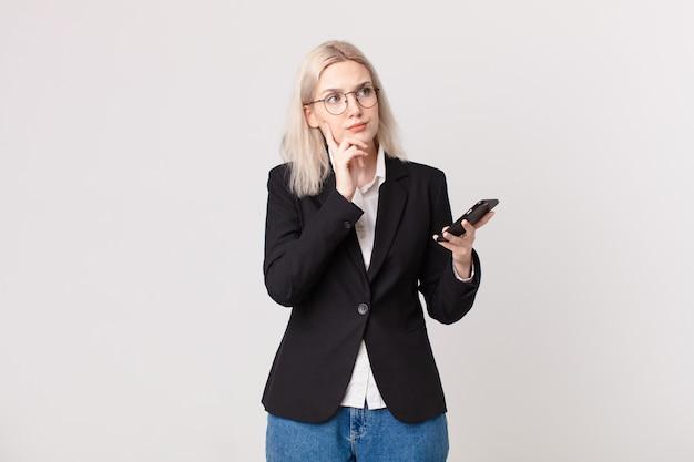 Jolie femme blonde pensant, se sentant dubitative et confuse et tenant un téléphone portable