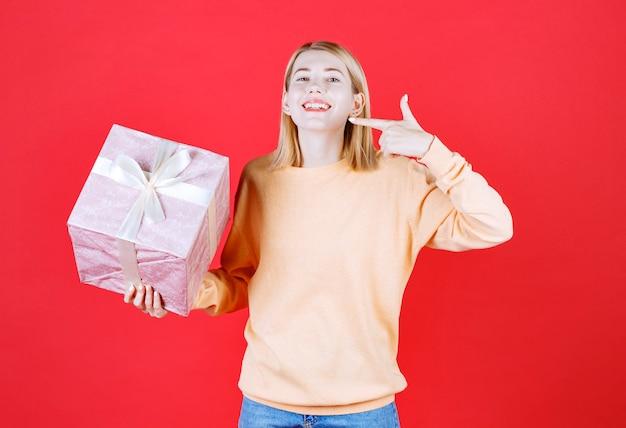 Jolie femme blonde pointe son sourire tout en tenant la boîte-cadeau devant le mur rouge