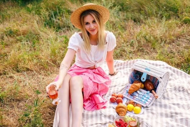 Jolie femme blonde portant une tenue de style vintage, profitant d'un pique-nique à la campagne dans un style français, buvant du vin avec des croissants et des fruits