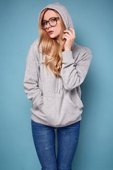 Jolie femme blonde positive à capuche grise et lunettes