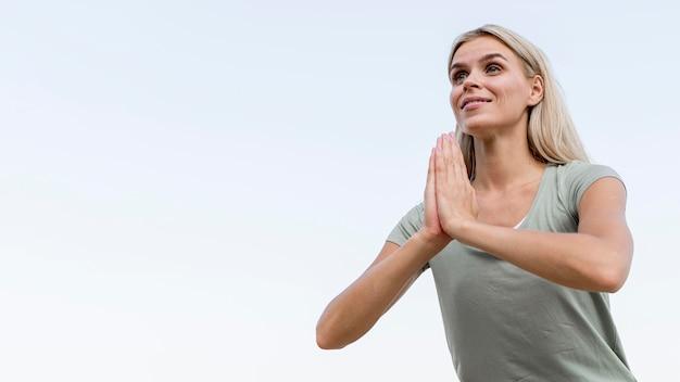Jolie femme blonde pratiquant le yoga à la plage