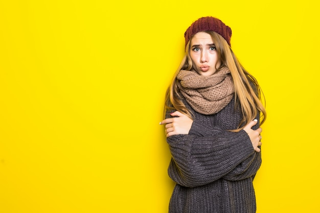 Jolie femme blonde en pull chaud essaie de se réchauffer
