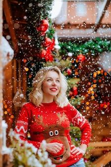 Jolie femme blonde en pull de noël rouge posant sur la terrasse en bois ouverte