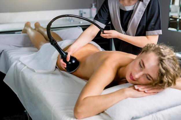 Jolie femme blonde recevant un traitement de remodelage du corps de la cavitation par ultrasons au salon de beauté moderne