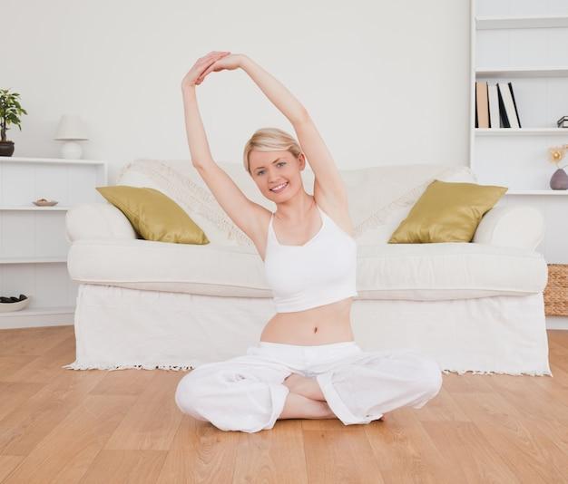 Jolie femme blonde en regardant la caméra tout en faisant des exercices de fitness