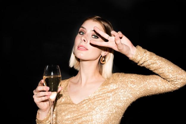 Jolie femme blonde en robe élégante en gardant la main avec un geste de paix par son œil et en faisant des toasts avec flûte de champagne à la fête