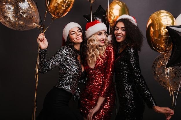 Jolie femme blonde en robe rouge célébrant les vacances d'hiver avec des amis