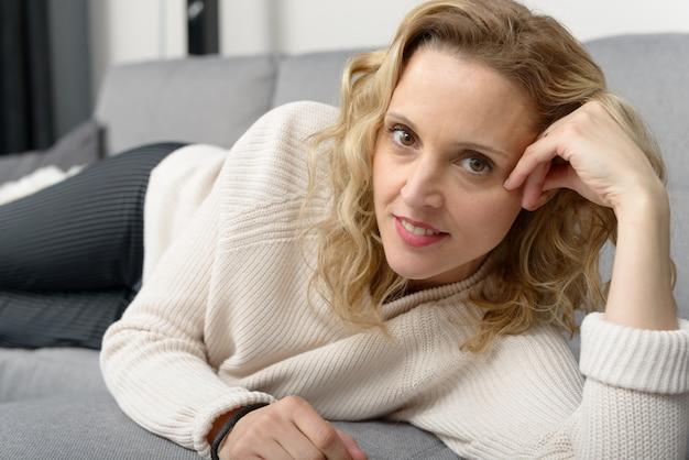 Jolie femme blonde se détendre sur le canapé dans sa maison