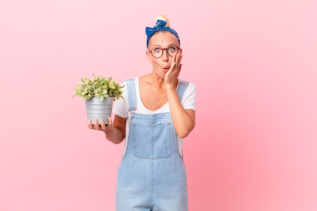 Jolie femme blonde se sentant choquée et effrayée et tenant une plante