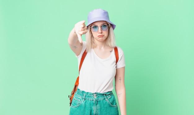 Jolie femme blonde se sentant croisée, montrant les pouces vers le bas. concept d'été