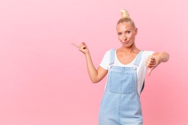 Jolie femme blonde se sentant croisée, montrant les pouces vers le bas