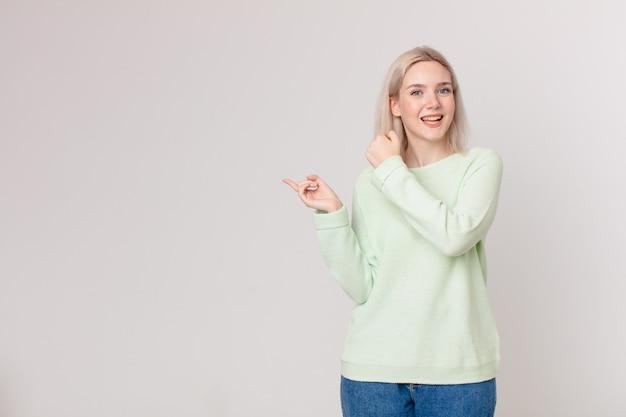 Jolie femme blonde se sentant heureuse et faisant face à un défi ou célébrant