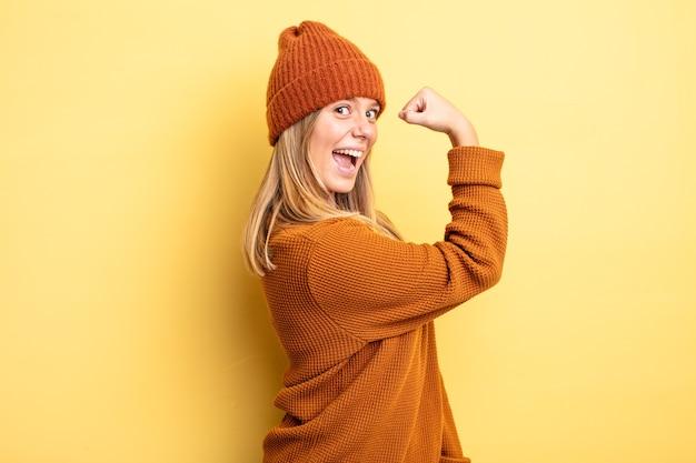 Jolie femme blonde se sentant heureuse, satisfaite et puissante, ajustement flexible et biceps musclés, ayant l'air fort après la salle de gym