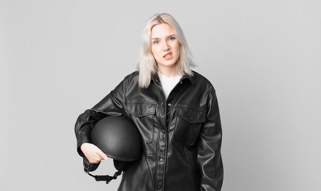 Jolie femme blonde se sentant perplexe et confuse. concept de motard