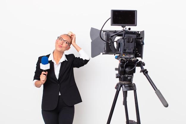 Jolie femme blonde se sentant perplexe et confuse, se grattant la tête et tenant un micro. concept de présentateur